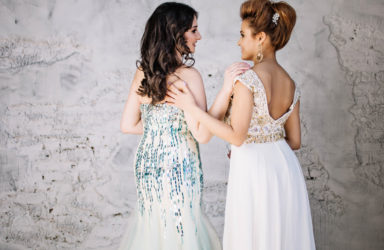 two girlfriends, beautiful girls in long evening dresses in the Studio, white brick background, backs, turned their heads to look at each other, profile, smiling